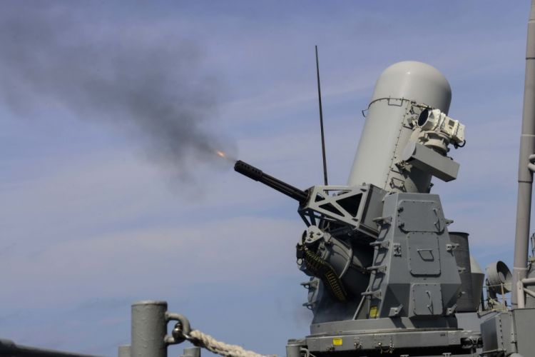 USS Normandyt firing its Phalanx weapons system