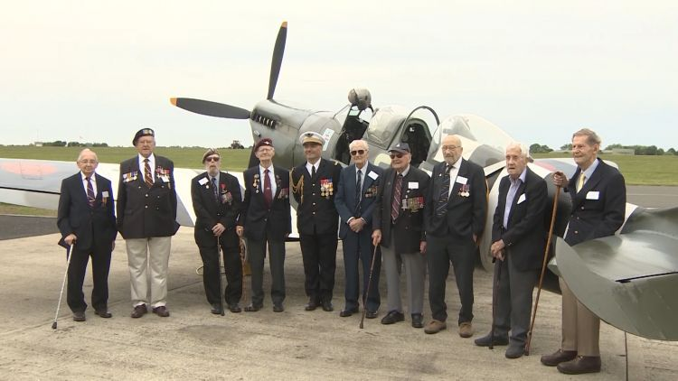 The veterans pose for a picture in front of the MJ772 Spitfire.