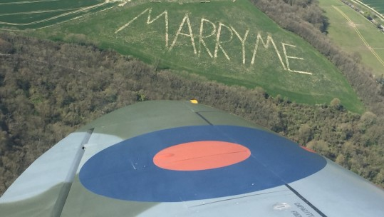 A pilot behind the controls of a WWII Spitfire was delighted when he discovered a giant marriage proposal - written in huge letters on a hill IMAGE BOULTBEE FLIGHT ACADEMY.jpg