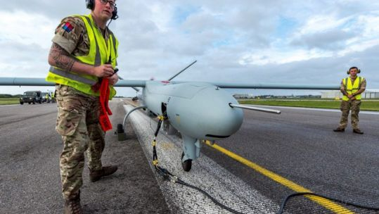 A soldier from 47 Regiment, Royal Artillery, removes safety warnings and covers from a Watchkeeper Unmanned Arial Vehicle at Lydd Airport, Kent