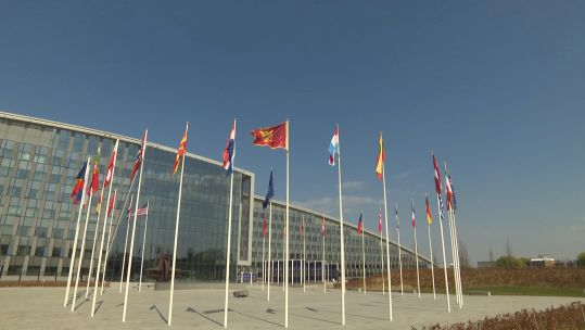 Alliance flags in foreground of NATO HQ exterior Brussels (Picture: NATO TV).