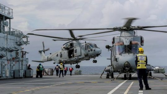 Anonymous military personnel and Merlin helicopters on the flight deck of RFA Argus whilst flying crucial disaster relief sorties to Honduras (Picture: MID