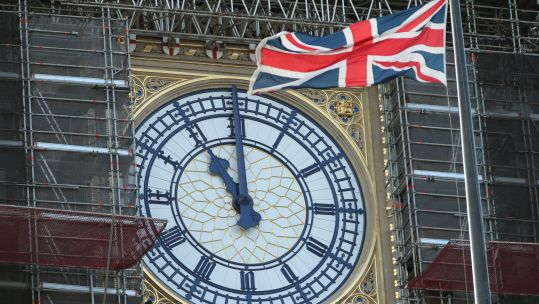 Big Ben Elizabeth Tower clock showing 11am at Westminster on Armistice Day 2019 with Union flag in foreground