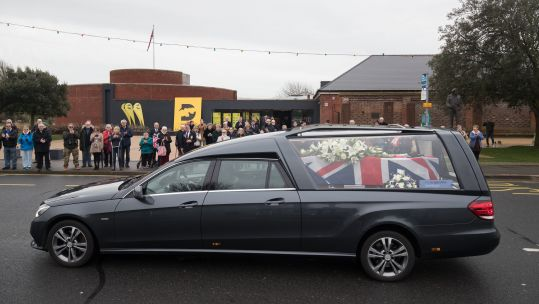 Cover Image: More than 100 people watched the funeral procession (Picture: PA).