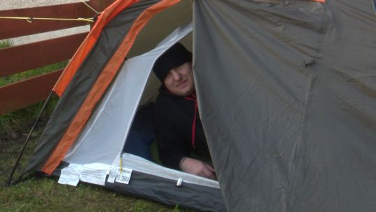 Gavin Dickinson Army Scripture Reader poses in his tent after a night sleeping outdoors for charity 250321 CREDIT BFBS