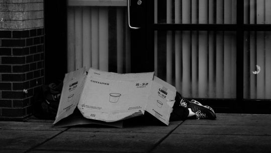Homeless person with cardboard SOURCE The Collab - Pexels