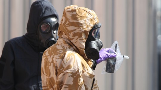 Investigators in chemical suits remove an item as they work behind screens erected in Rollestone Street, Salisbury, Wiltshire.jpg