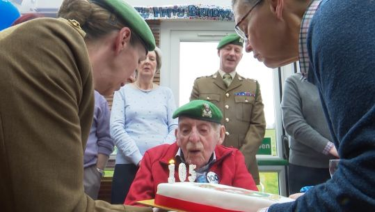 Captain Oldfield blowing out the candles on his cake.