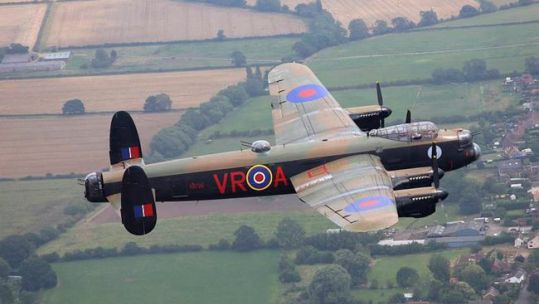Avro Lancaster bomber flying over English European countryside