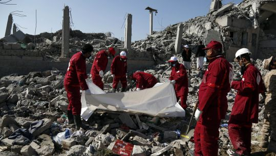 Local Red Crescent medics carry the body of a victim following the air strikes (Picture: PA).