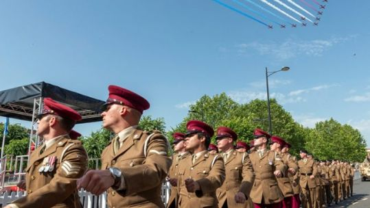 Personnel parade on Salisbury Armed Forces Day under Red Arrows flypast