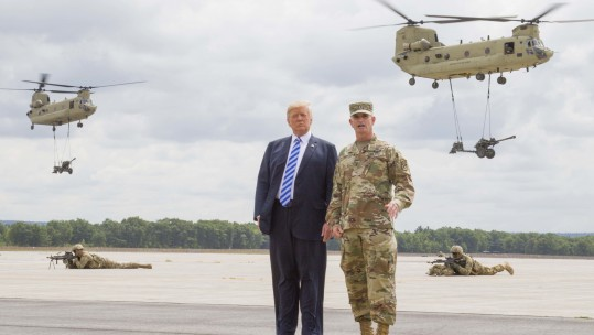 President Donald J. Trump and Maj. Gen. Walter E. Piatt, commander of the 10th Mountain Division (LI), look on as CH-47 Chinook helicopters carry in artillery during a demonstration at Fort Drum, New York, Aug 13 CREDIT DVIDS