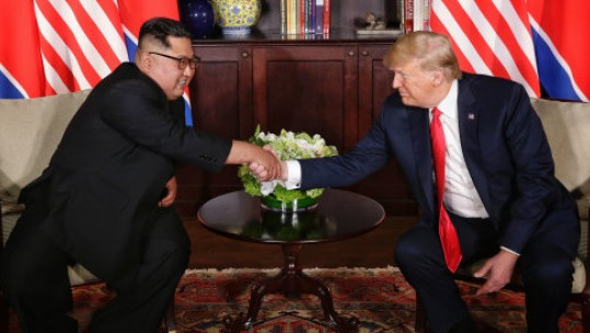 President Donald Trump and Kim Jong Un shake hands