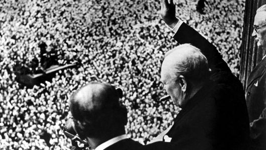 Prime Minister Winston Churchill gives his famous V for Victory sign to a crowd of 50,000 from balcony of Ministry of Health on VE Day
