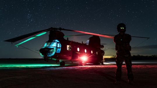 A Royal Air Force CH-47 Chinook helicopter rests at night during a training mission in the Arizona desert. The chinook was being used at a FARP to refuel USMC helicopters (Picture: RAF).