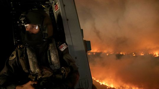 Cover Image: A Royal Australian Navy aircrewman over the wildfires in New South Wales (Picture: Australian Defence Force).