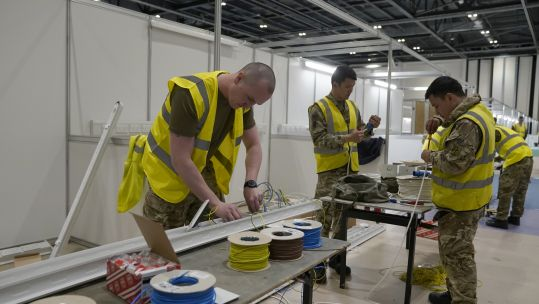 Cover image: Soldiers help work together to build NHS Nightingale (Picture: Number 10/Flickr).