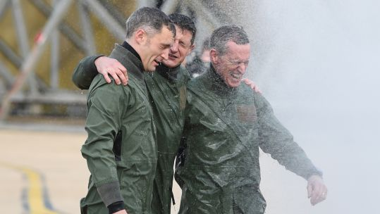Squadron Leader Chris Whitehair, Croup Captain Ian Townsen and Air Chief Marshal Sir Stephen Hillier getting soaked at RAF Marham