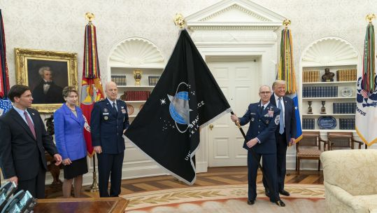 US Space Force CSO GEN Jay Raymond and US Space Force Senior Enlisted Advisor CMSgt Roger Towberman present US President Donald Trump with the US Space Force Flag (Picture: PA).